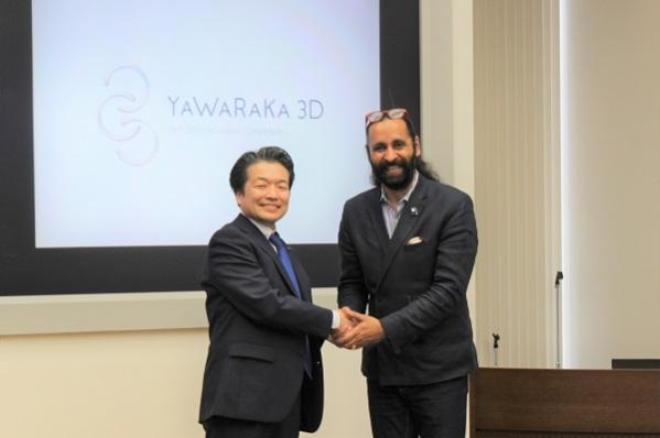180416やわらか3D01: 古川会長と、背景のコンソーシアムのロゴをデザインしたマンジョット・ベディ氏(just on time社)