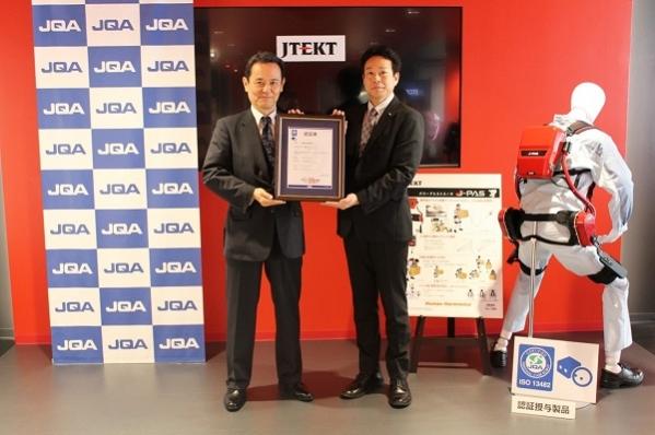 180824ジェイテクト: 認証書授与のようす:日本品質保証機構 理事 浅田純男氏(写真左)とジェイテクト 新規事業推進部 第1推進室 室長 尾崎 光晴氏(写真右)